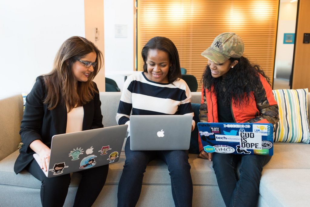 three woman in front of laptop computer